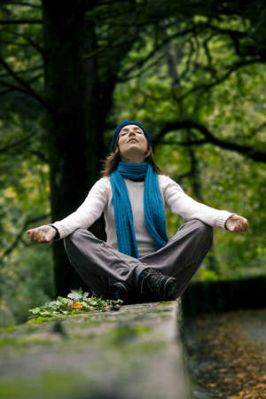 Beautiful young woman in nature making meditation exercises photo
