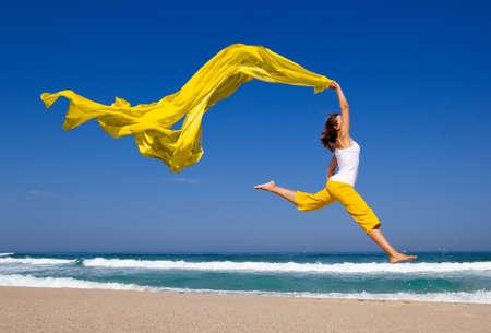 persona saltando: Joven y bella mujer saltando en la playa con un tejido color