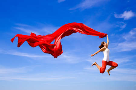 Schöne junge Frau, die einen Sprung über den blauen Himmel mit einem farbigen Gewebe