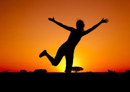 Silhouette of a young woman jumping at the sunset Stock Photo - 7954983