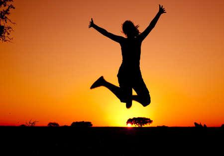 feeling positive: Silueta de una mujer joven saltando en la puesta de sol