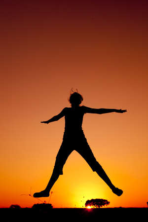 happiness people silhouette on the sunset: Silhouette of a young woman jumping at the sunset Stock Photo