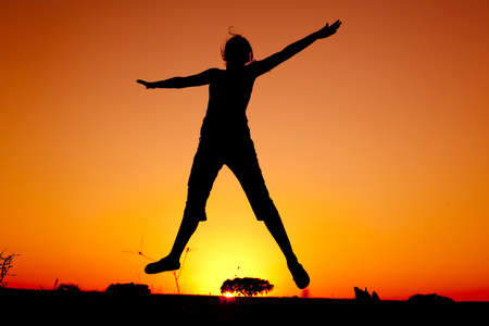 Silhouette of a young woman jumping at the sunset Stock Photo - 7955009