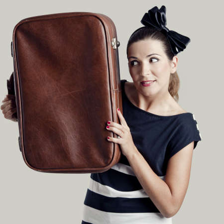 Portrait of a beautiful fashion woman posing and holding a old suitcase photo