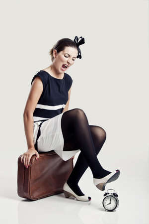Beautiful young fashion woman sitting over a suitcase and smashing a clock photo