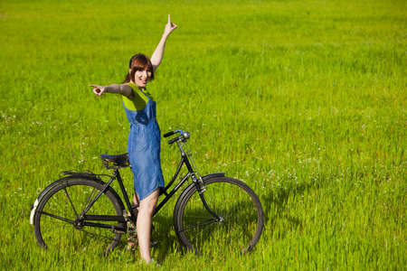 Happy young woman with a vintage bicycle on a green meadow Stock Photo - 7955019