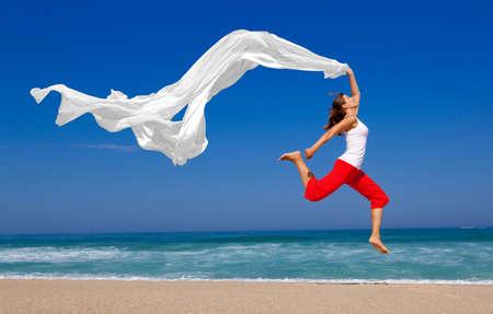 Schöne junge Frau, die am Strand mit einem farbigen Gewebe springen Standard-Bild