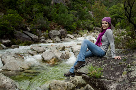 Outdoor portrait of a beautiful young woman sitting on a rock photo
