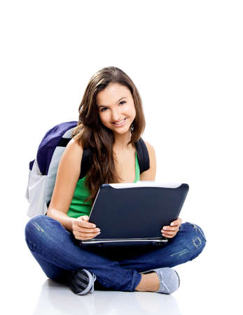 Beautiful young female student sitting on floor studying on a laptop, isolated on white Stock Photo - 8104054