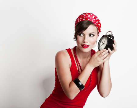 Beautiful and fashion young woman with a pin-up look holding a clock photo