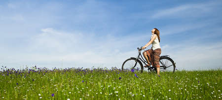 freedom park: Happy young woman with a vintage bicycle on a green meadow Stock Photo