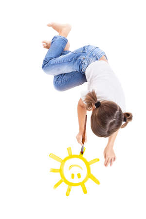 Top view of a happy girl lying on floor and painting a happy sun photo