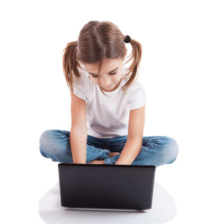 Little girl sitting on floor working with a laptop Stock Photo - 8307701