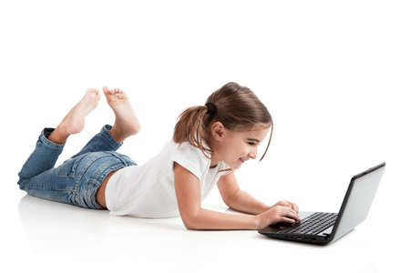 Little girl lying on floor working with a laptop