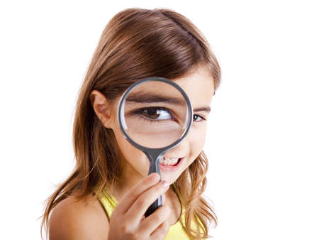 Beautiful little girl looking through a magnifying glass photo