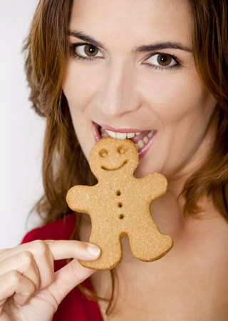 Close-up portrait of a beautiful young woman bitting a gingerbread cookie photo