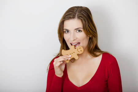 Beautiful young woman bitting a gingerbread cookie photo