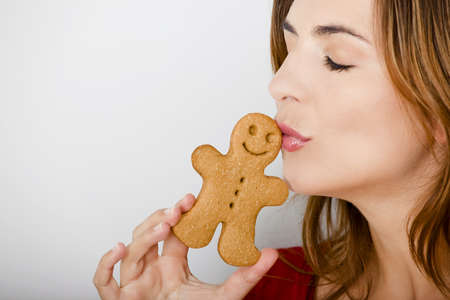 Beautiful young woman kissing a gingerbread man cookie photo