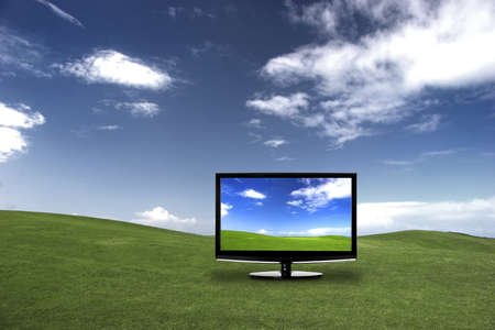 than: Modern television on a green meadow, showing the colors more beautiful than reality Stock Photo