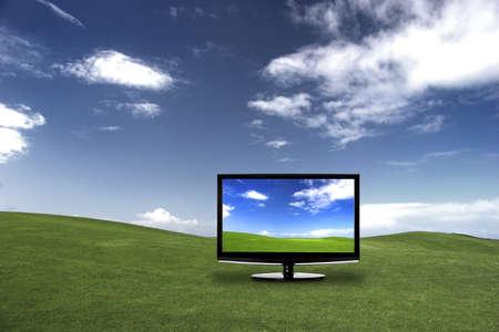 Televisi�n moderno en un prado verde, mostrando los colores m�s bellos que la realidad Foto de archivo - 8372431
