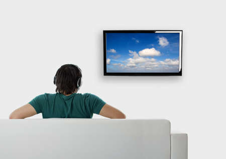 watching tv: Rear view from a young man seated on the couch watching tv Stock Photo