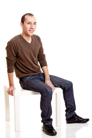smilling: Portrait of a young man seated and smilling, isolated on white Stock Photo