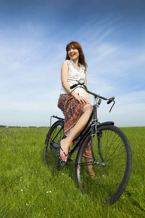 Happy young woman on a green meadow with a vintage bicycle photo