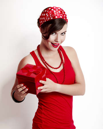 Beautiful and fashion young woman with a pin-up look holding a gift box photo