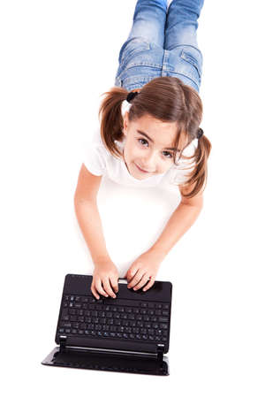 Top view of a little girl lying on floor working with a laptop photo