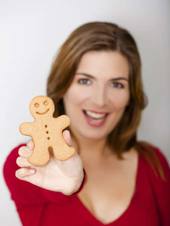 Beautiful young woman holding a gingerbread cookie, focus is on the ginger man Stock Photo - 8458456