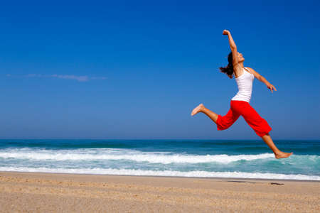 Beautiful young woman jumping on  the beach Stock Photo - 8647441