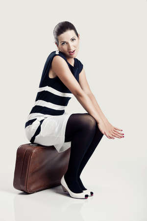 Portrait of a beautiful fashion woman sitting over an old suitcase Stock Photo - 8647420