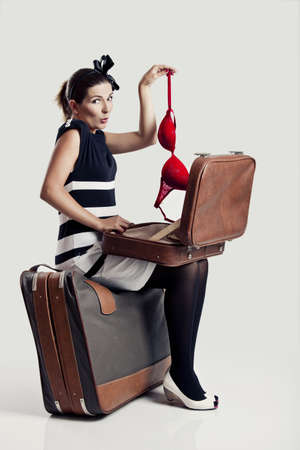 Beautiful young fashion woman opening a suitcase and holding a red under braw photo