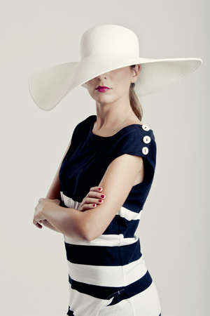 Portrait of a beautiful fashion woman posing with a hat photo