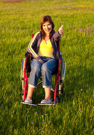 handicapped person: Happy handicapped woman with thumbs up seated on a wheelchair over a green meadow Stock Photo