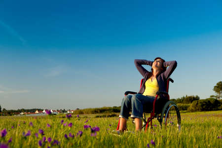 Wheel chair: Handicapped woman on a wheelchair over a green meadow