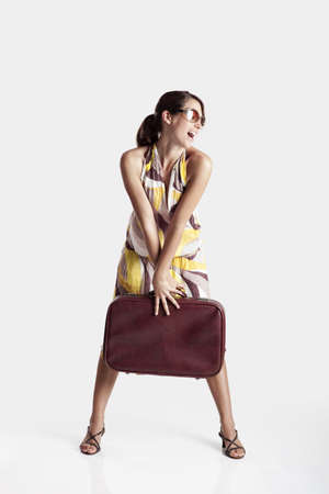 Beautiful young fashion woman posing with a old suitcase photo