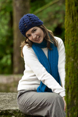 Outdoor portrait of a beautiful young woman sitting on a stone wall photo