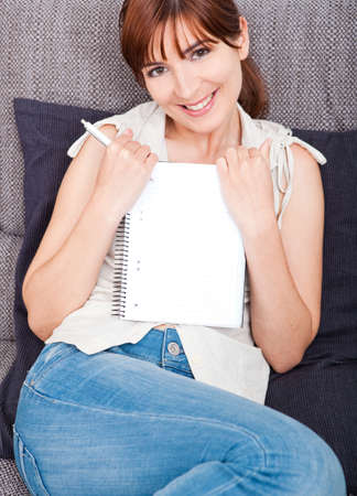 Woman sitting on couch and showing something on a notebook photo