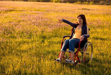 Wheel chair: Happy handicapped woman on a wheelchair over a green meadow pointing and looking away Stock Photo