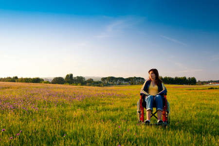 blue sky thinking: Happy handicapped woman on a wheelchair over a green meadow looking away Stock Photo