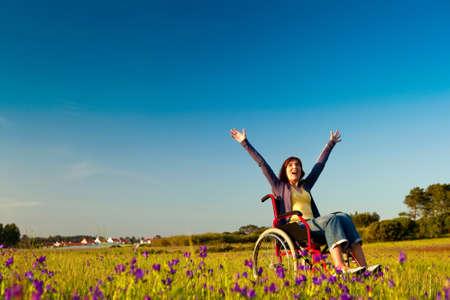 personas discapacitadas: Mujer con discapacidad feliz en una silla de ruedas en un prado verde