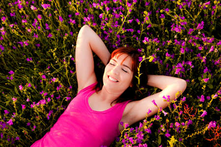 Top view of a beautiful young woman lying on a flowery meadow photo