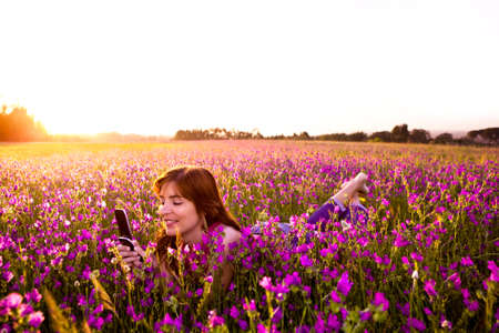Beautiful young woman lying on the nature and talking at cellphone  photo