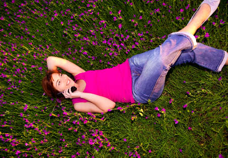 Top view of beautiful young woman lying on the nature and talking at cellphone  photo