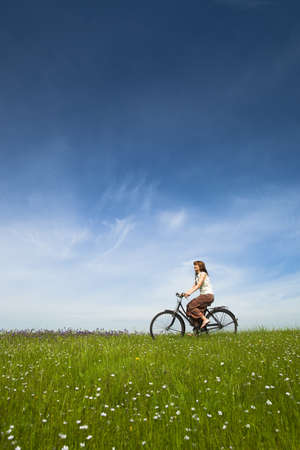 Happy young woman on a green meadow riding a bicycle Stock Photo - 8735410