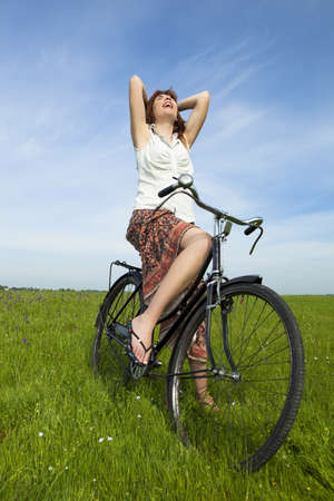 Happy young woman on a green meadow with a vintage bicycle Stock Photo - 8735438