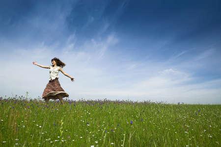 Young woman dancing on a beautiful green meadow photo