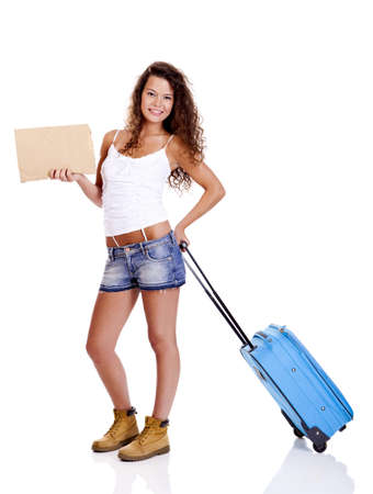 Beautiful young woman carrying a blue suitcase and holding a cardboard, isolated on white background photo