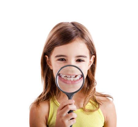 dentition: Bella ragazza mostrando teethes attraverso una lente di ingrandimento